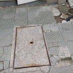 Типичен софийски тротоар - ръждясала шахта и счупени плочки, с тук-таме наредени на ръка парченца.
